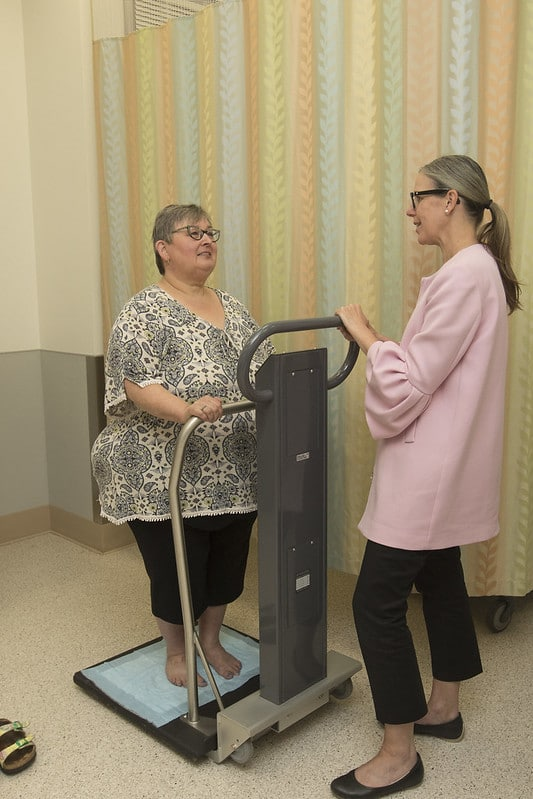 The image depicts an obese women, on a weighing scale, who is being monitored for weight loss maintenance.
