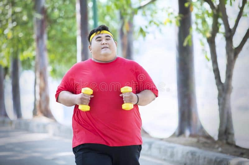 An obese man running with dumbbells in hands.