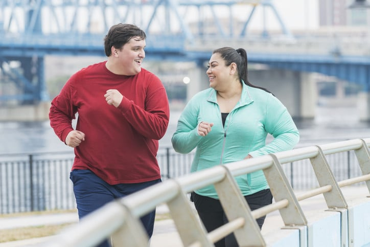 A couple with obesity exercising together, i.e. fat but fit.